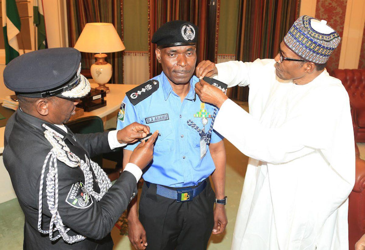 President Muhammadu Buhari decorates the new Inspector General of Police, Mr Mohammad Abubakar Adamu at the State House Abuja, on Tuesday, January 15, 2019.  PHOTO: SUNDAY AGHAEZE
