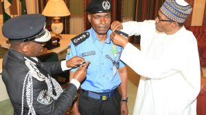 President Buhari Muhammadu Buhari decorates the new Inspector General of Police, Mr Mohammad Abubakar Adamu at the State House Abuja, on Tuesday, January 15, 2019.  PHOTO: SUNDAY AGHAEZE